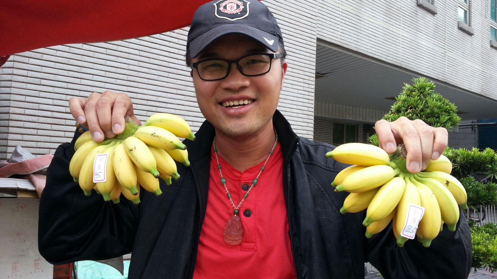 Jeff, an OWNRIDES driver, holding up two bunches of bananas while smiling