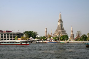 Boats cruising down the Chao Praya River, passing by the Temple of Dawn - Wat Arun
